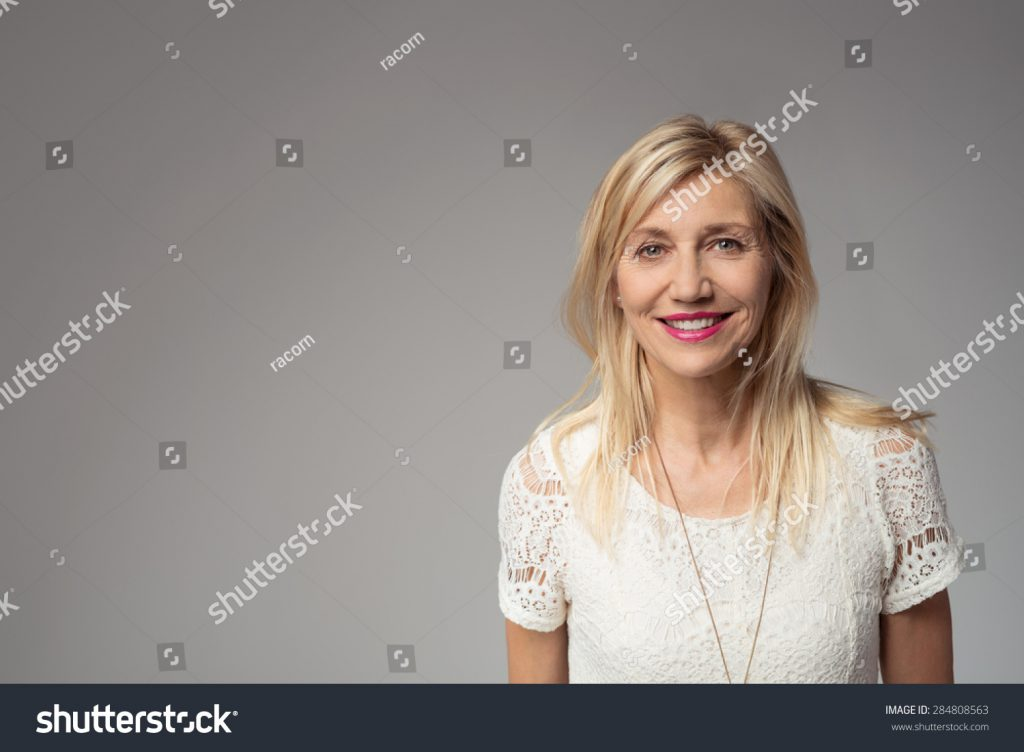 stock-photo-close-up-smiling-blond-adult-woman-looking-at-the-camera-against-gray-background-with-copy-space-284808563