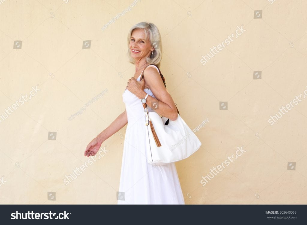 stock-photo-portrait-of-happy-older-woman-in-summer-dress-walking-with-purse-603640055
